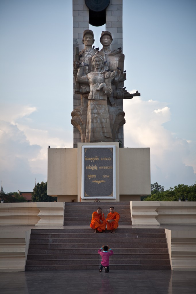 Monks ask a passing boy to take their photo in front of the Vietnamese Friendship Monument